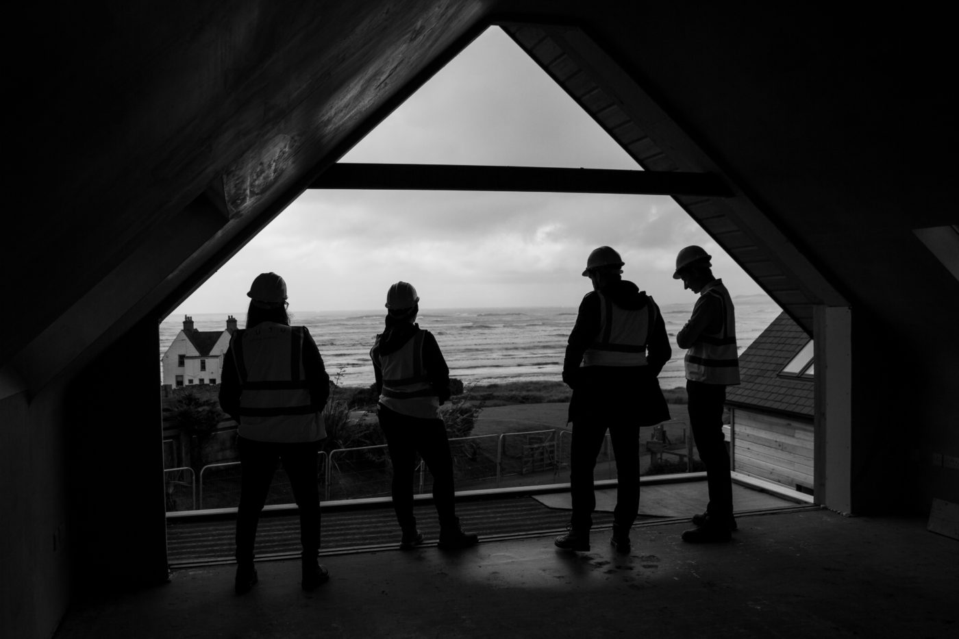 Black and white image of architects looking over the sea